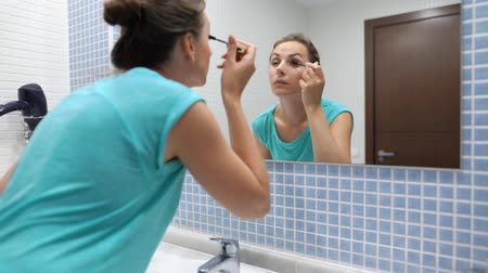 щеткой : Pretty woman applying black mascara for eyelashes makeup in front of bathroom mirror