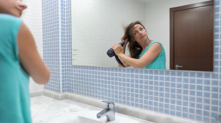щеткой : Pretty woman blows her hair in front of bathroom mirror