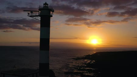stone : View from the height of the lighthouse Faro de Rasca, nature reserve and dark clouds at sunset on Tenerife, Canary Islands, Spain. Wild Coast of the Atlantic Ocean Stock Footage