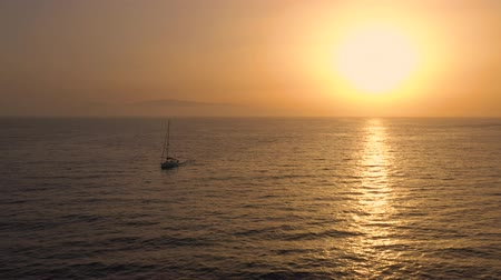 vízfelület : Aerial view of surface of the Atlantic Ocean on the background of a beautiful sunset. Yacht returns to the marina Stock mozgókép