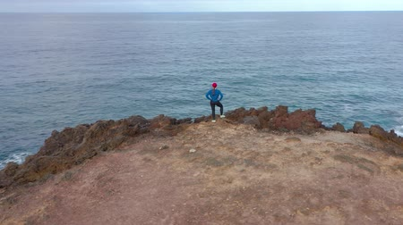 vítr : Aerial view of woman in sportswear after jogging stands on top of a rock and enjoys the scenery in a conservation area on the shores of the Atlantic Ocean. Tenerife, Canary Islands, Spain