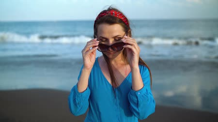 luksus : Portrait of a woman in a beautiful blue dress on a black volcanic beach. Slow motion