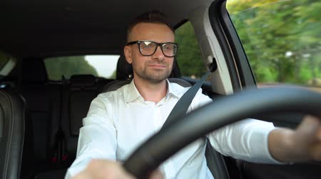 motoring : Bearded man in glasses and white shirt driving a car in sunny weather