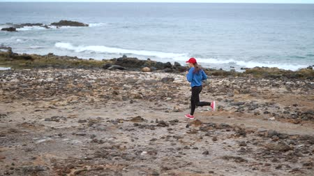závodní dráha : Woman runs along the stony shore of the ocean. Healthy active lifestyle