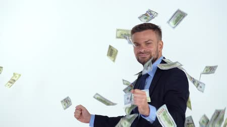 ganancioso : Slow motion of formally dressed man is delighted with the fact that a lot of dollar bills are fall on him