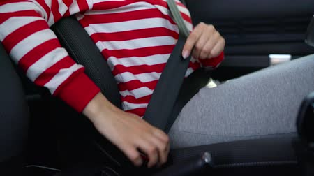 tutturma : Woman fastening car safety seat belt while sitting inside of vehicle before driving