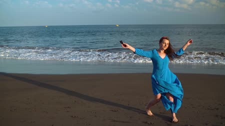 boho : Woman in a beautiful blue dress and sunglasses enjoys a walk along the beach, joyfully spinning. Slow motion
