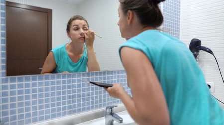seu : Woman does a morning routine - brushes her teeth, does makeup and puts her hair on.