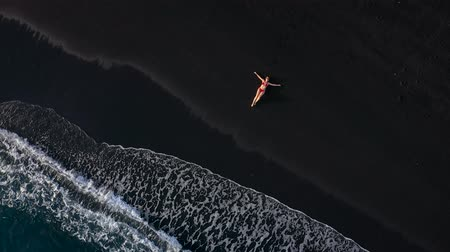 mentiras : Top view of a girl in a red swimsuit lying on a black beach on the surf line. Coast of the island of Tenerife, Canary Islands, Spain.