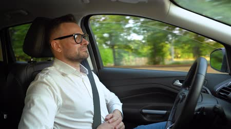 przyszłość : Bearded man in glasses and white shirt driving a car in sunny weather and uses autopilot function while driving