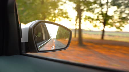 doux : View from the rearview mirror as car drives through the road surrounded by trees at sunset