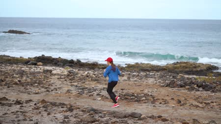 visszaszámlálás : Woman runs along the stony shore of the ocean. Healthy active lifestyle. Slow motion Stock mozgókép