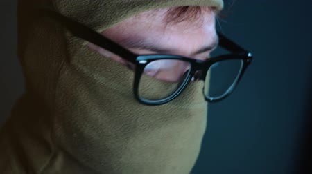 włamywacz : Male hacker in the mask on face and glasses working on a computer in a dark office room. Cybercrime concept
