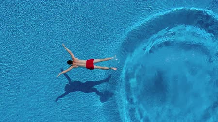 flutuador : View from the top as a man dives into the pool and swims under the water Stock Footage