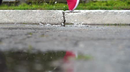 pozzanghera : Legs of a runner in sneakers. Sports woman jogging outdoors, stepping into muddy puddle. Single runner running in rain, making splash. Slow motion