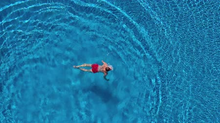 sprengstoff : View from the top as a man dives into the pool like a bomb and swims under the water