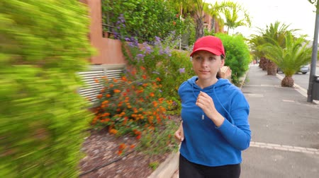 uliczka : Woman jogging along the street among the tropical alley Wideo