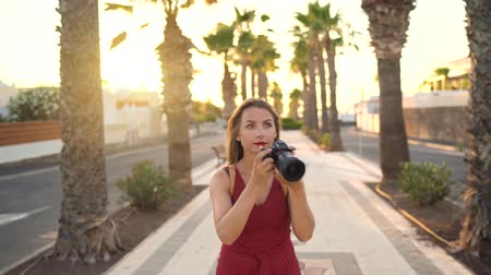 写真 : Photographer tourist woman taking photos with camera in a beautiful tropical landscape at sunset
