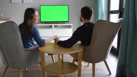 dialog : Man and woman are sitting in chairs, kissing and watching TV with a green screen, switching channels with a remote control. Back view. Chroma key. Indoors