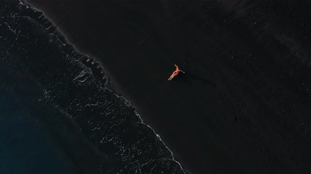 hazugság : Top view of a girl in a red swimsuit lying on a black beach on the surf line. Coast of the island of Tenerife, Canary Islands, Spain.