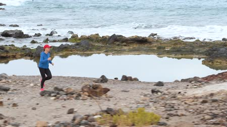 visszaszámlálás : Woman runs along the stony shore of the ocean. Healthy active lifestyle