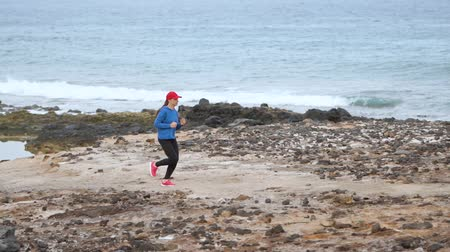 acabamento : Woman runs along the stony shore of the ocean. Healthy active lifestyle