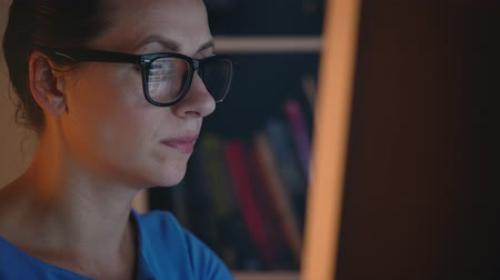 nagyító : Woman in glasses looking on the monitor and surfing Internet. The monitor screen is reflected in the glasses Stock mozgókép