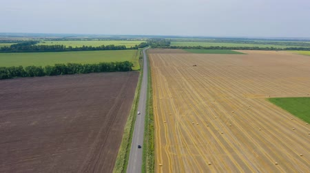 szénaboglya : Top view of the road and cars driving along it. On the sides of the road are fields during harvest