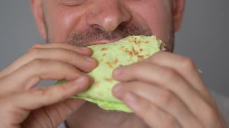 маслянистый : Man eating spinach shawarma with chicken and vegetables close-up