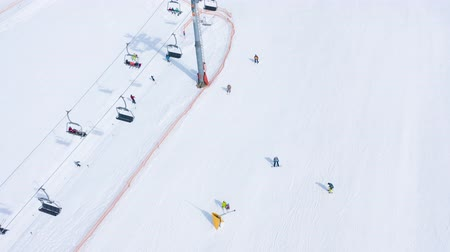 hegyoldalban : Aerial hyperlapse of ski slope - ski lift, skiers and snowboarders going down Stock mozgókép