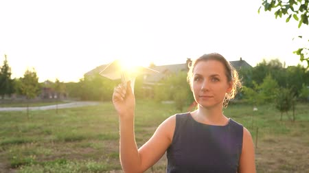 zabawka : Woman launches paper airplane against sunset background. Dreaming of traveling or the profession of a stewardess Wideo