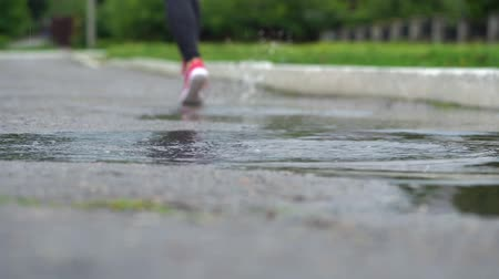 trilhas : Legs of a runner in sneakers. Sports woman jogging outdoors, stepping into muddy puddle. Single runner running in rain, making splash