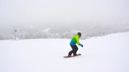 montanhas rochosas : Extreme snowboarder riding fresh powder snow down the steep mountain slope