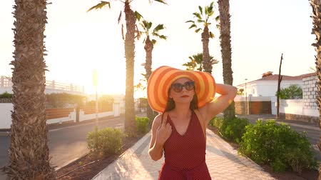 locatie : Happy woman in a big yellow hat walking along a palm alley at sunset