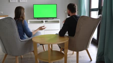 zatáčka : Man and woman are sitting in chairs, watching TV with a green screen, discuss what they saw and switching channels with a remote control. Back view. Chroma key. Indoors Dostupné videozáznamy