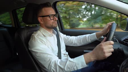 driveway : Bearded man in glasses and white shirt driving a car in sunny weather and uses autopilot function while driving