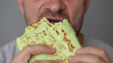 olejnatý : Man eating spinach shawarma with chicken and vegetables close-up