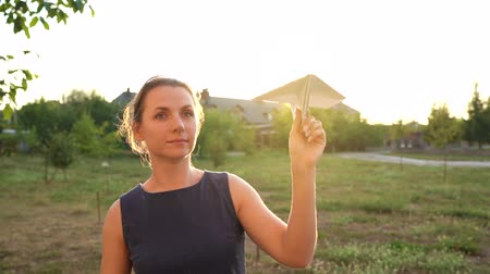 авиационно космический : Woman launches paper airplane against sunset background. Dreaming of traveling or the profession of a stewardess. Slow motion Стоковые видеозаписи
