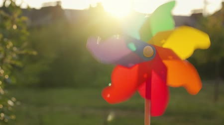 glare : Plastic rainbow windmill rotates against the setting sun Stock Footage
