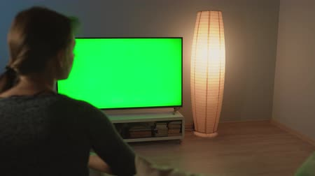 narożnik : Woman is sitting on the couch, watching TV with a green screen, switching channels with a remote control. Chroma key. Black cat in the corner of the room Wideo