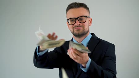 ganancioso : Slow motion of formally dressed man scatters dollar bills around him, making money rain