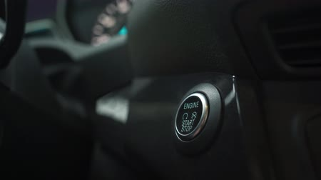 gyújtás : Male hand pushes engine start stop button in a modern car interior
