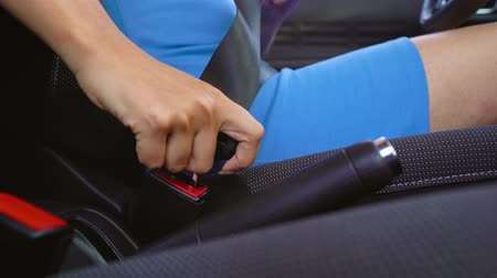 přezka : Woman in blue dress fastening car safety seat belt while sitting inside of vehicle before driving