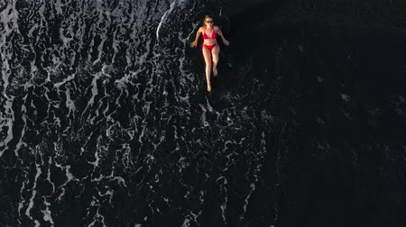 mentiras : Top view of a woman in a red swimsuit lying on a black beach on the surf line. Coast of the island of Tenerife, Canary Islands, Spain.