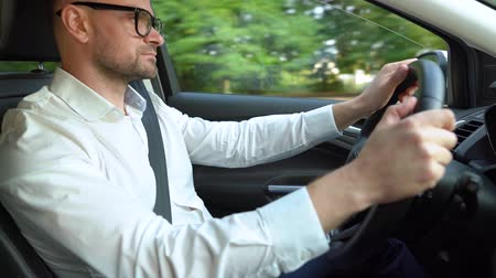 motoring : Bearded man in glasses and white shirt driving a car in sunny weather. Side view