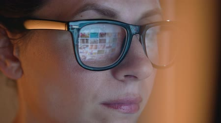 makler : Woman in glasses looking on the monitor and surfing Internet. The monitor screen is reflected in the glasses Wideo