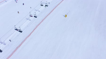 hegyoldalban : Aerial view of ski slope - ski lift, skiers and snowboarders going down Stock mozgókép