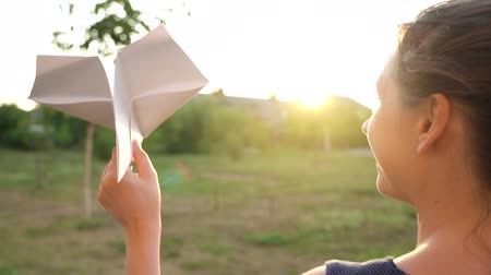 sunrise light : Woman launches paper airplane against sunset background. Dreaming of traveling or the profession of a stewardess. Slow motion Stock Footage