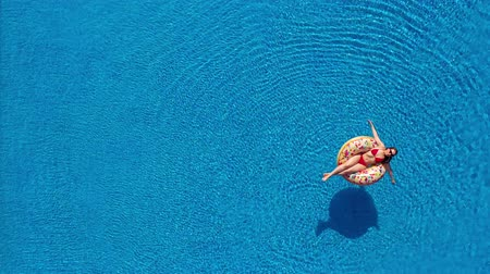 doughnut : Aerial view of a woman in red bikini lying on a donut in the pool Wideo