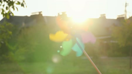propeller toy : Plastic rainbow windmill rotates against the setting sun Stock Footage